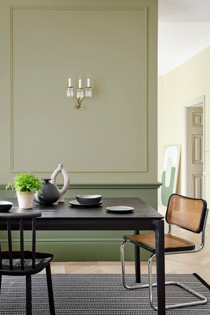 Sage green dining room with black table and cane chairs