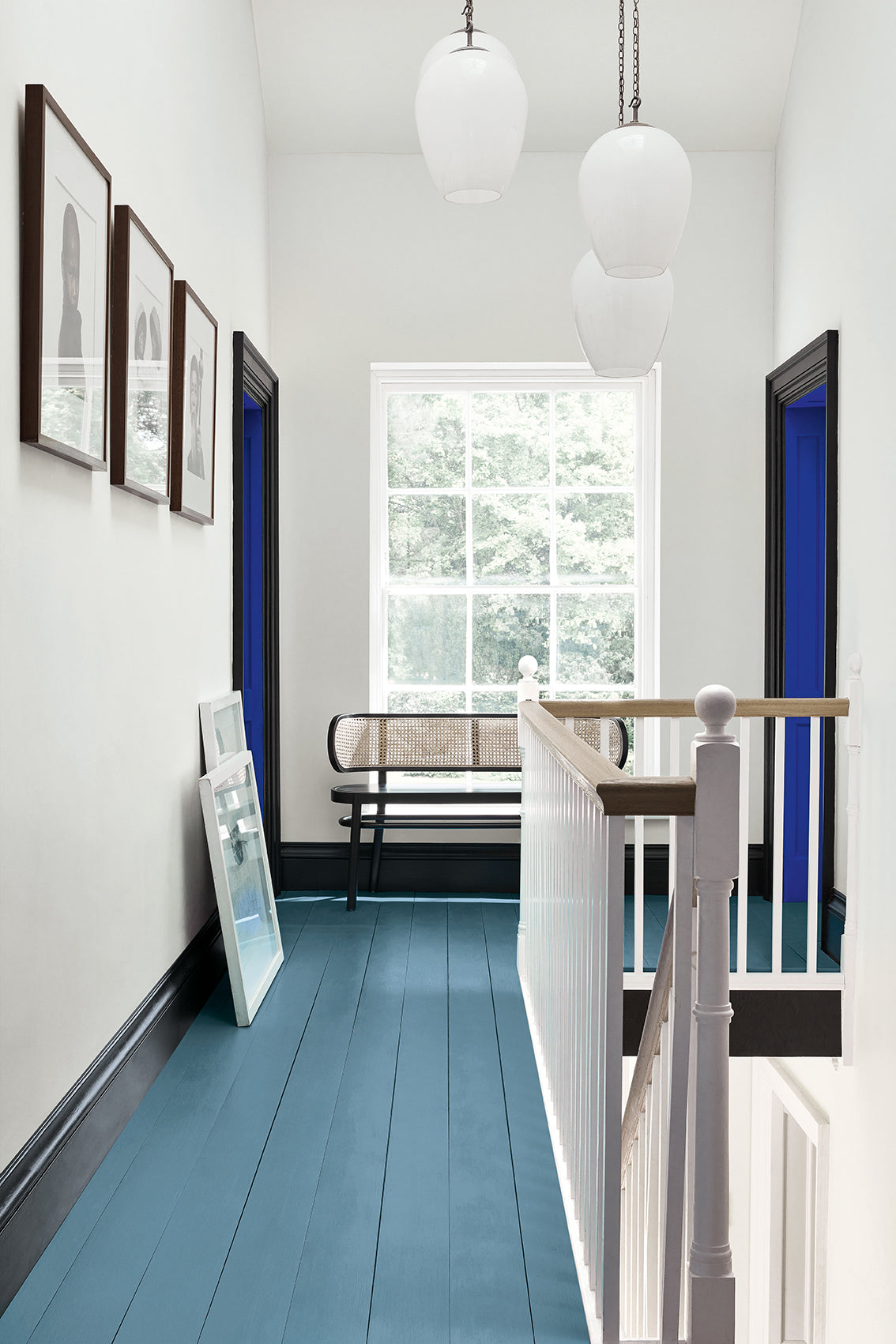 Landing with bright blue floorboards, and contrasting skirting and doors