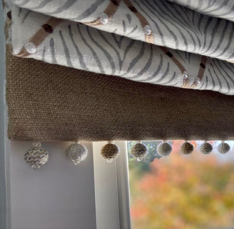 close up of cascade waterfall roman blind showing contrast bottom panel and bobble trim
