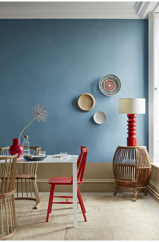 Bright blue dining room with cane furniture and contrasting red lamps