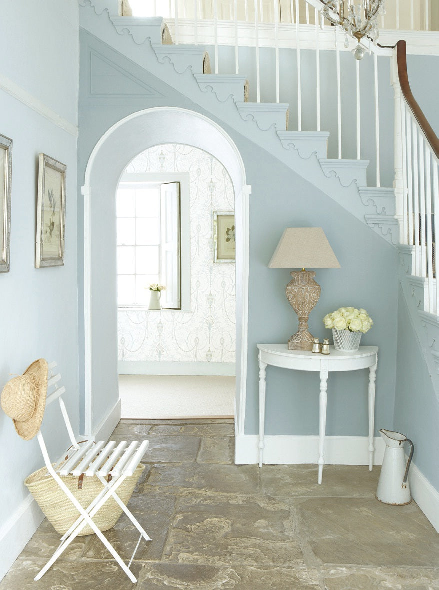 Hallway painted in pale blue with white woodwork & staircase