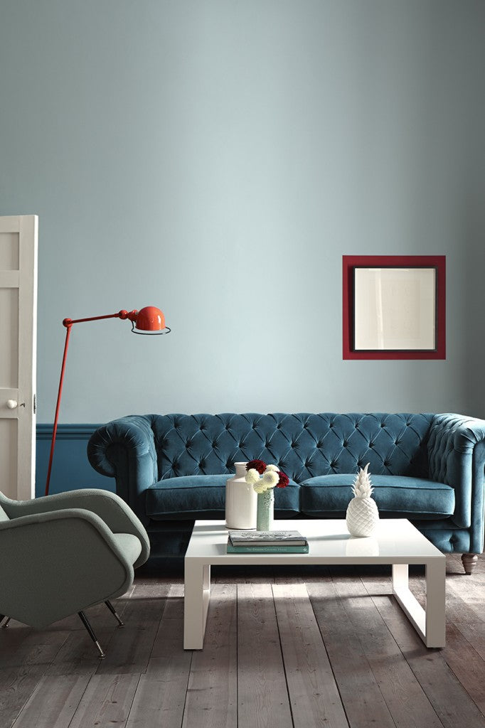 Pale blue painted living room with petrol blue velvet sofa and orange arc lamp