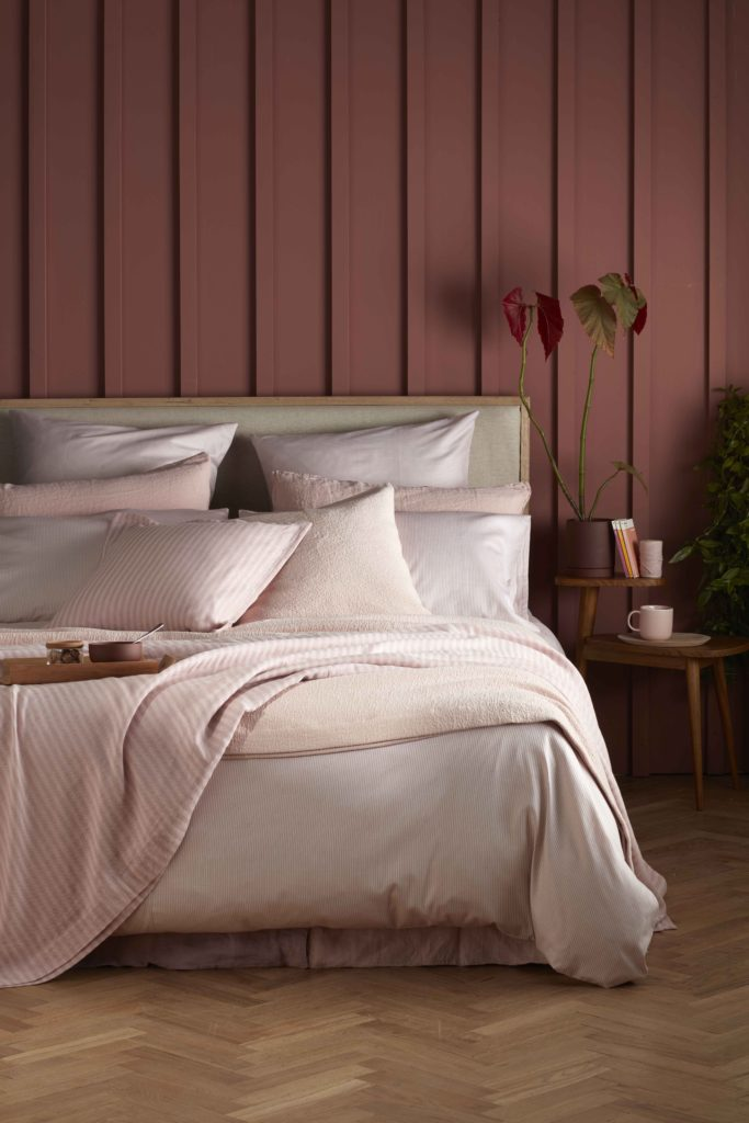 Dusky pink panelled bedroom with tumbled pale pink bedlinen