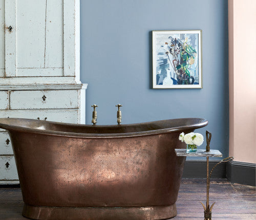 Bathroom painted mid blue and soft pink with a copper roll top bath and vintage white dresser