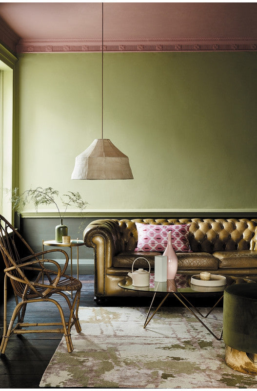 Living room with walls painted in two shades of green, and ceiling in blush pink
