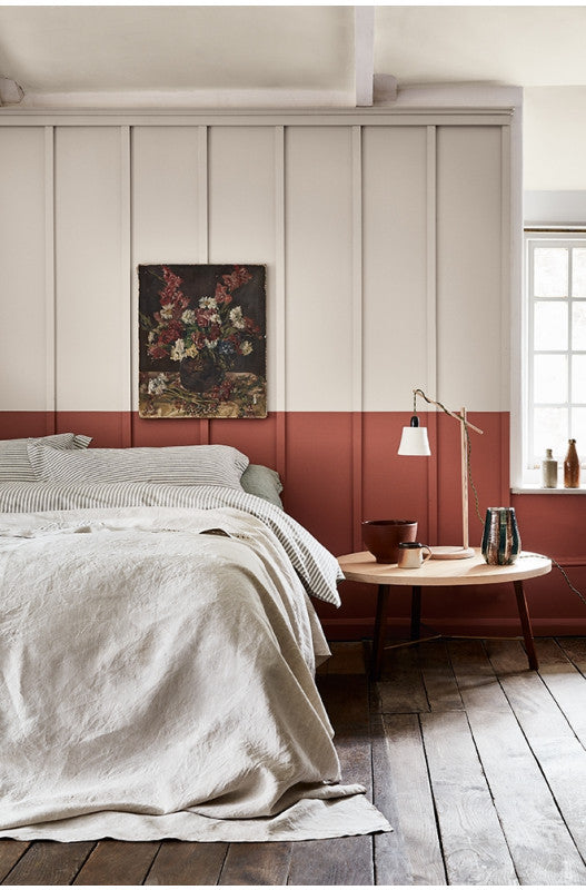 Bedroom in natural shades of stone and terracotta with linen bedding & wooden floorboards