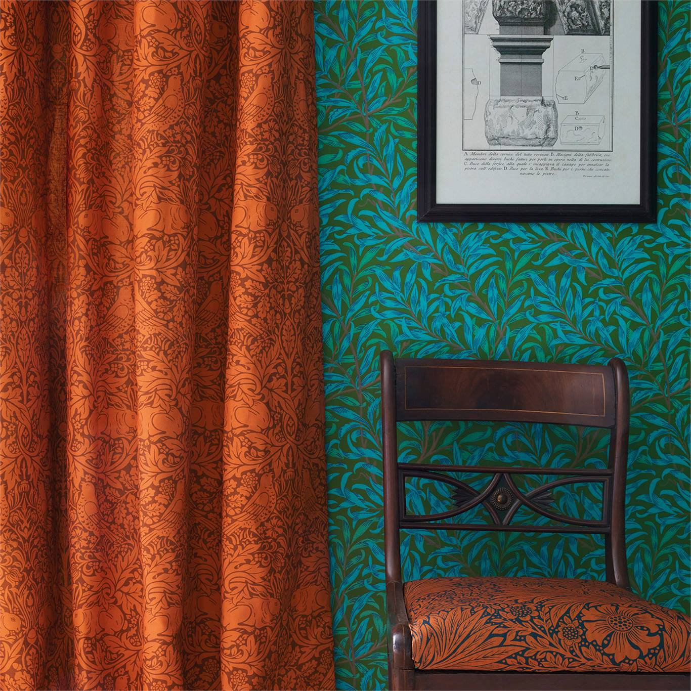 Rust coloured curtains and upholstered chair against marine blue wallpaper
