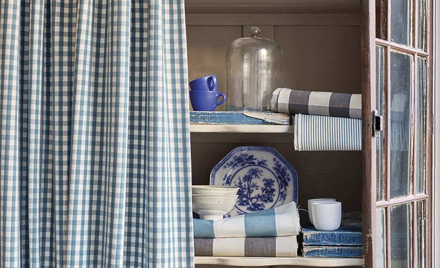 Close up picture of gingham curtains and folded striped fabrics in an armoire