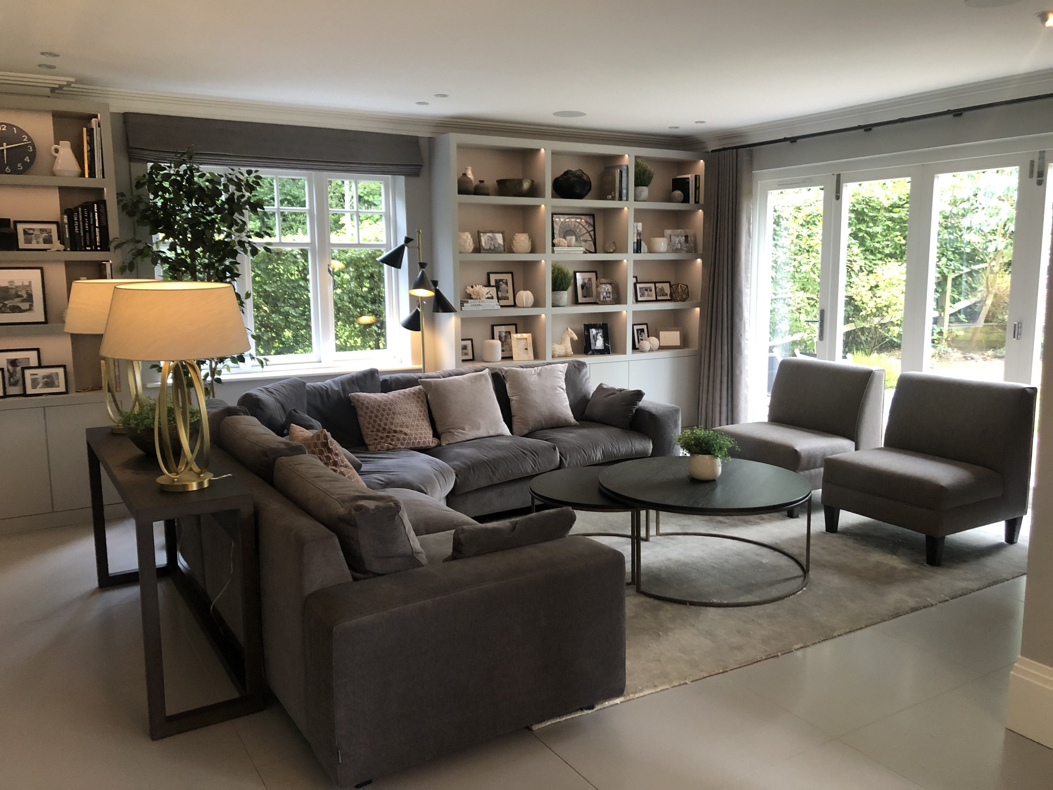 French Grey walls and bespoke cabinets, dark grey sofa, mint rug, pink armchairs, putty curtains and blind, bronze lamps and fittings