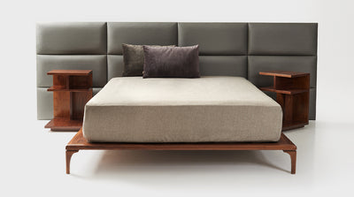 An upholstered, grey, panel headboard with a slim walnut bed base.