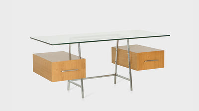 A contemporary desk with a glass top, chrome legs and two oak drawers with long, slim, steel handles.