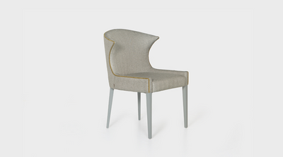 A dining chair that is inspired by classic Scandinavian and Mid-Century design. It has smooth curves and grey coloured, mahogany, tapered legs. It features tailored ecru coloured upholstery and a beautiful mustard coloured piping detail.