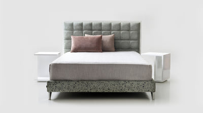 A bed set that has a grey upholstered headboard, with a block stitch detail, and a white timber frame. It also has a grey upholstered bed base that has steel legs.