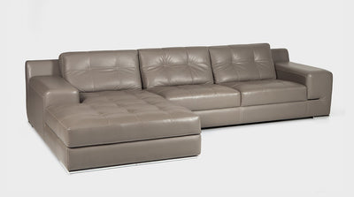 A Stone leather sofa with a chaise and wide arms. The upholstery is enhanced by a white block stitch detail on the cushions and a double stitch detail on the base.