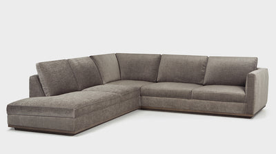 A stone grey contemporary corner sofa with an oak base, one arm and a chaise.