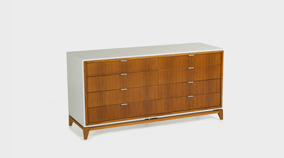 A mid-century chest of drawers with eight, walnut, drawers and slim silver handles. It has a white frame and walnut legs.