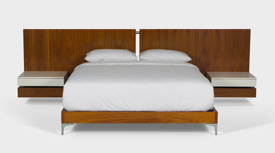 A linear, walnut timber bed with floating pedestals and silver accents, front view.