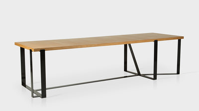 A contemporary dining table with a rectangular, oak top and a black, powder coated, steel base that has an unconventional geometric design.