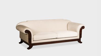 A classic sofa with luxury cream upholstery and ornate hand carvings of lotuses and scrolls on its mahogany frame.