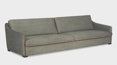 A fully upholstered, grey, contemporary sofa that has orange piping, slim arms and is extra depth.