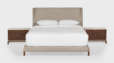 A contemporary bed with an upholstered bed base and head board which features a slight wingback. The base has unique, walnut timber legs.