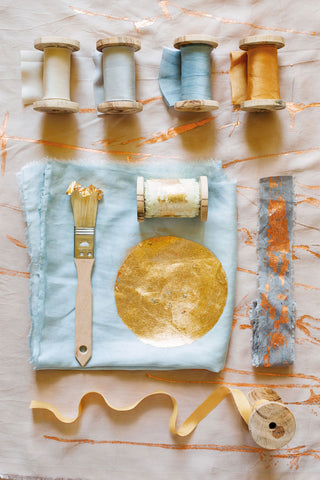 Plant dyed silk ribbons with gold leaf sun on textiles, displayed on wooden spools with paintbrush