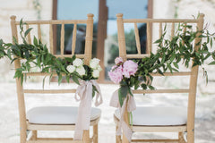 Two wedding chairs at Spanish wedding venue adorned with pink and white flowers and trailing silk ribbons