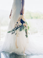 Model wearing white wedding gown holding bridal bouquet with flowing silk ribbons