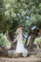 Spanish olive grove wedding venue with bride in front of tree holding bouqeut with trailing silk ribbons