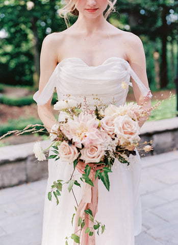 Model in bride dress holding bouqeut of pink roses tied with soft blush pink ribbon