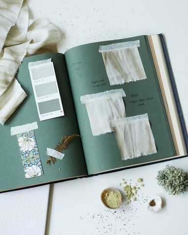 Artist notebook with green colour inspiration, plant dyed silk ribbons, weld seeds and weld powder