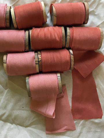 Shades of orange and peach silk ribbons on wooden spools