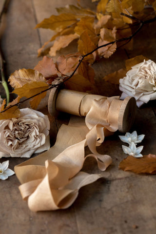 Gold and taupe silk ribbons on a spool with leaves and foliage on a table.
