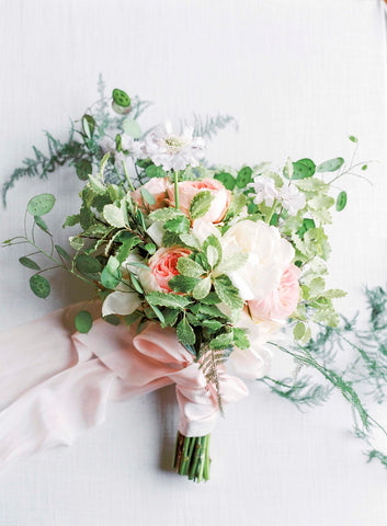 Pink and white flowers in bridl bouquet tied with plant dyed silk ribbons