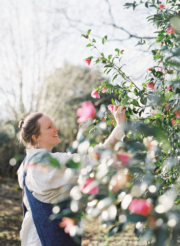 Lady looking at pink camellias