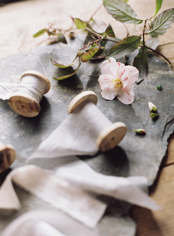 Two spools of plant dyed silk ribbon in shades of pale pink and grey displayed on table