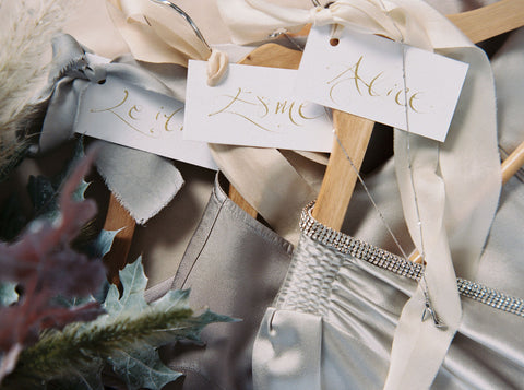 4 wooden hangers with soft grey dresses tied with pale grey and ivory silk ribbons