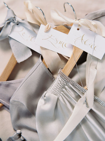 4 wooden dress hangers tied with grey and ivory silk ribbons and hung with silver necklaces and charms