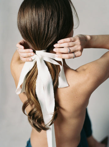 Back of models hair with silk ribbon tied in a bow at base of a low pony tail