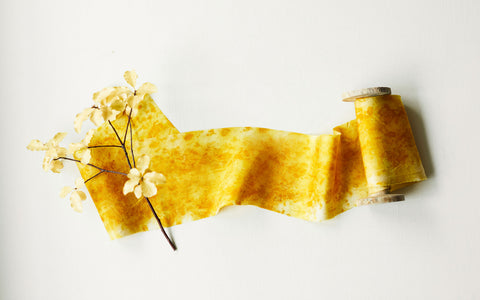 Yellow silk ribbon unwound from a wooden spoolwith foliage
