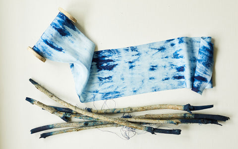 Indigo patterned silk shibori ribbon on a wooden spool with river sticks dyed at tips with indigo