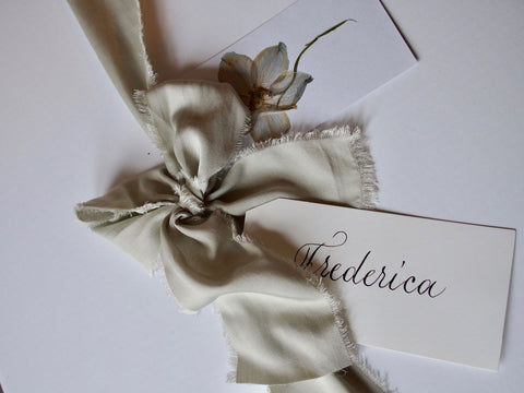 Grey green silk ribbon tied around a luxury white hamper with name tag