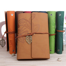 Load image into Gallery viewer, Photo of our classic style journals with cord and metal leaf to secure and close the notebook - several colors available
