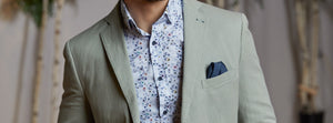 Man wearing light grey cotton blazer with blue floral sport shirt and navy pocket square. Men's essential wardrobe item.