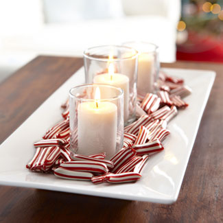 white dish with white candles surrounding by peppermint candies