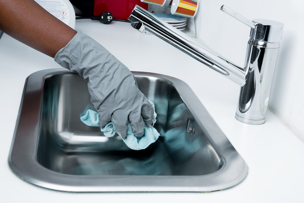 Gloved hand cleaning a sink