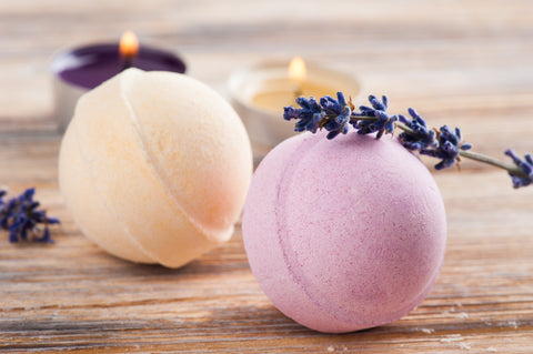CBD lavender bath bomb recipe – two bath bombs, one pink and one peach, on a wooden table covered by sprigs of lavender.
