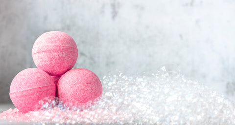3 pink bath bombs placed in a bath tub with rising bubbles coming from the tub.