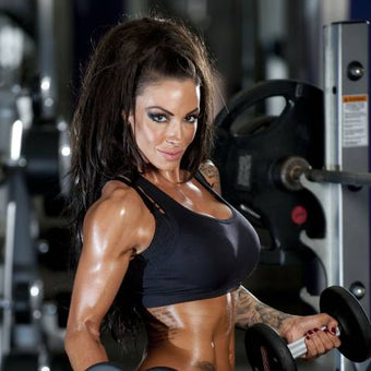 Photograph of model and bodybuilder Jodie Marsh in black gym clothes lifting weights