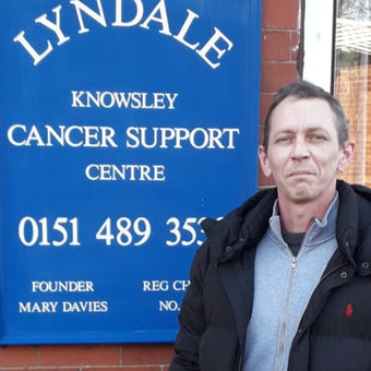Photograph of Shaun Walsh in front of a blue Lyndale Knowsley Cancer Support Centre sign